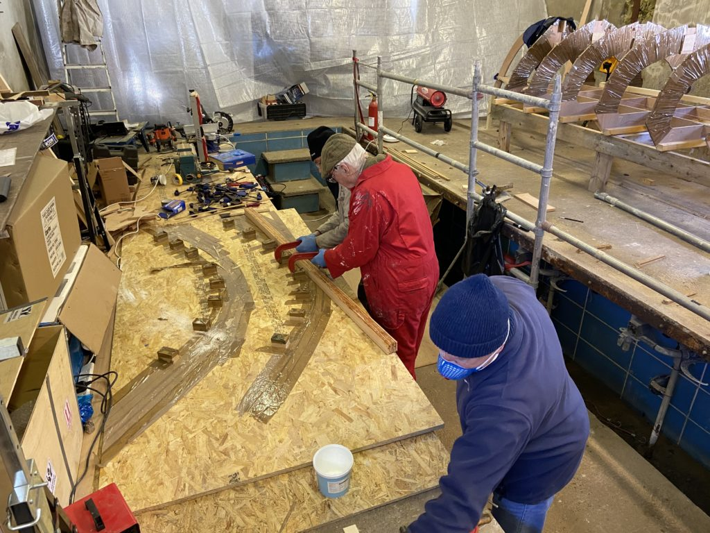 Martyn Webster in red leading the work party, assembling skiff parts