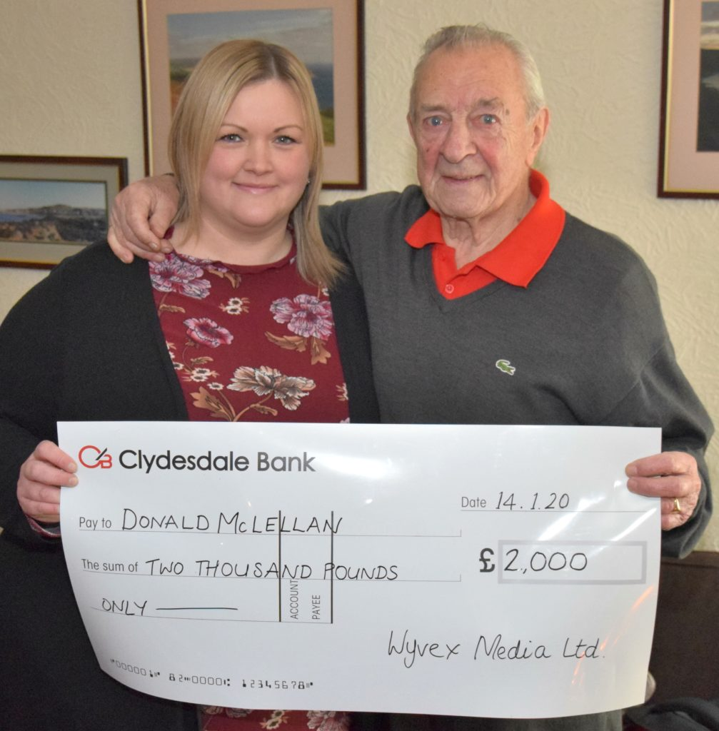 Donald receives his cheque for £2,000 from the Courier's Rebecca Harvey.