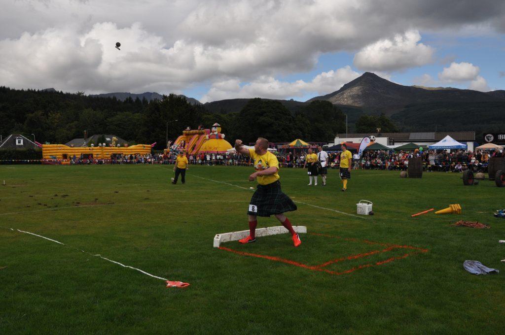 Ernie Weir throws the 28lb for distance.