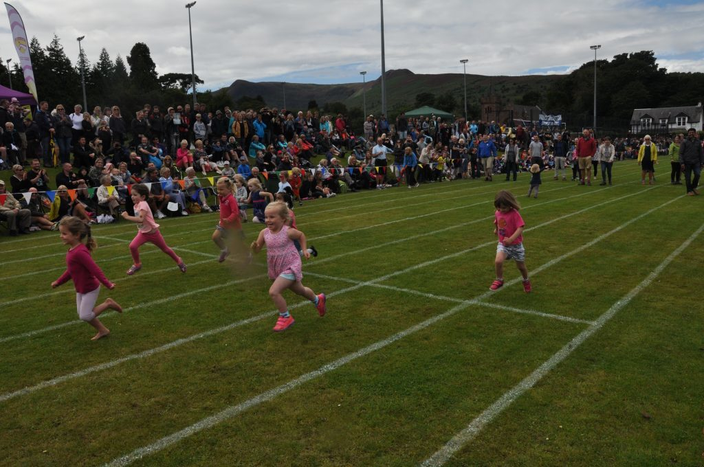 A big crowd watch a childen's race.