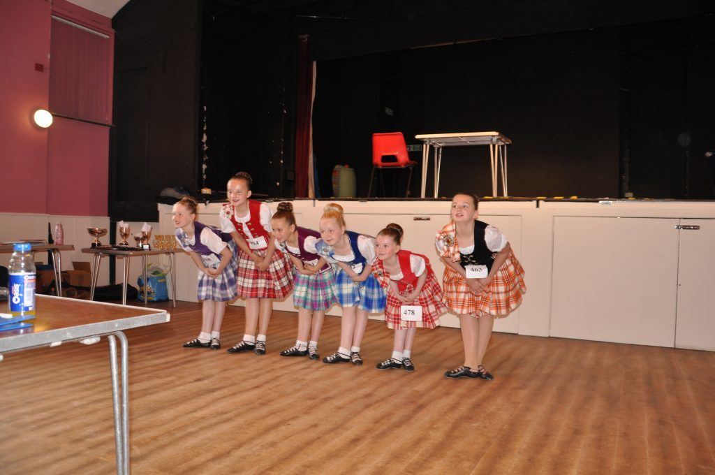 Highland dancers take a bow after collecting their medals.