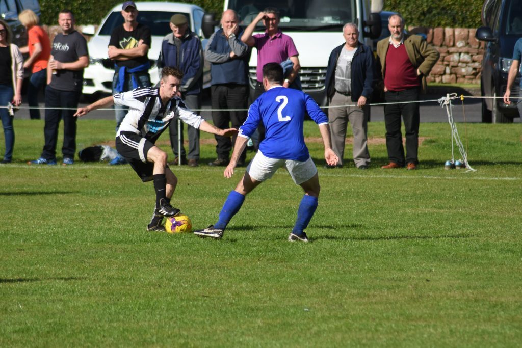 Fancy footwork by Lamlash player Johnny Sloss sees him slip past his opponent