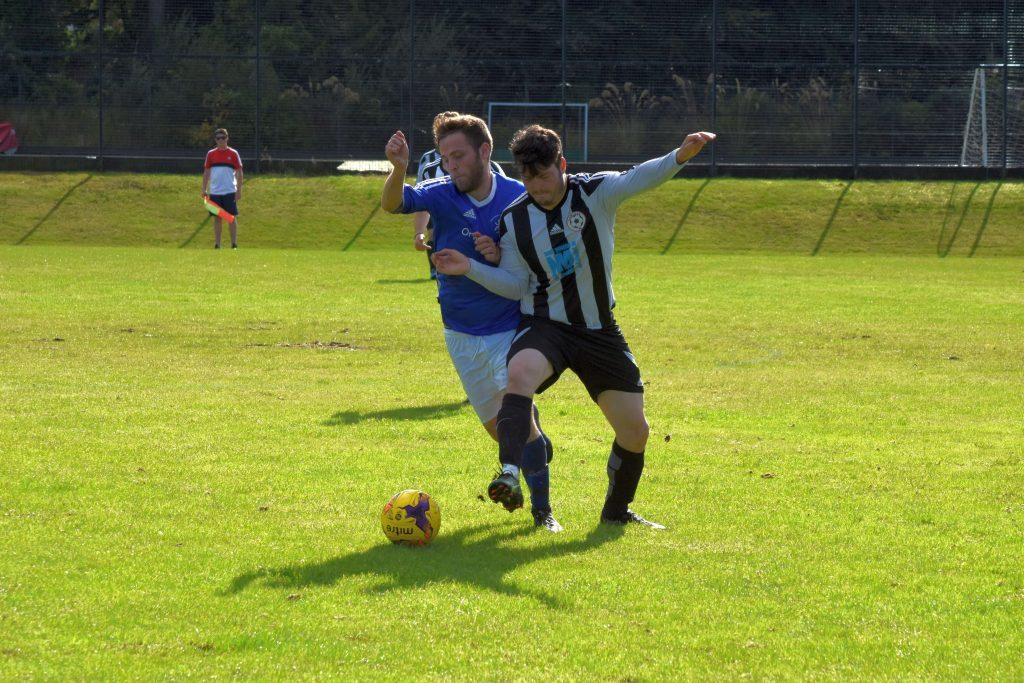 Brodick goal scorer Babbies MacNeil tussles with the opposition to lay claim to the ball