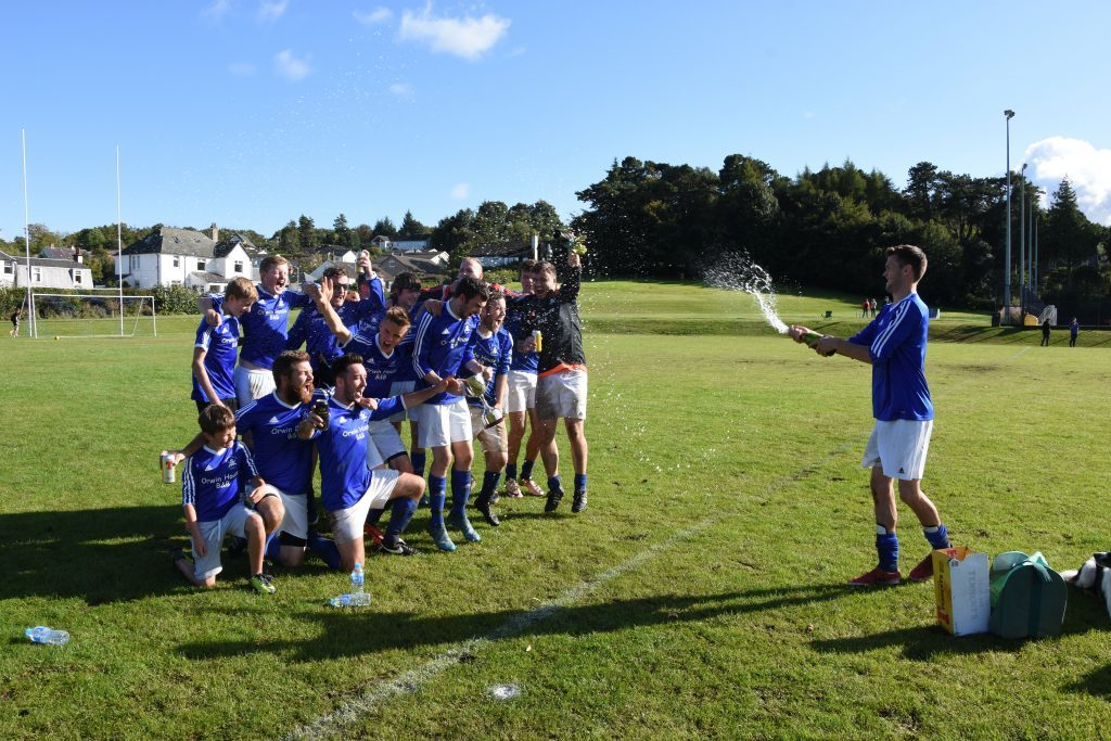 Brodick captain Matthew Dobson showers the jubilant winners with champagne