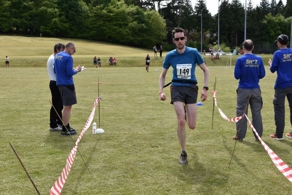 First local male Malcolm Wilkinson crosses the finish line.