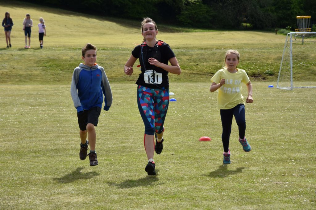 First time runner, Abbie Mckelvie, crosses the line with two supporters alongside.