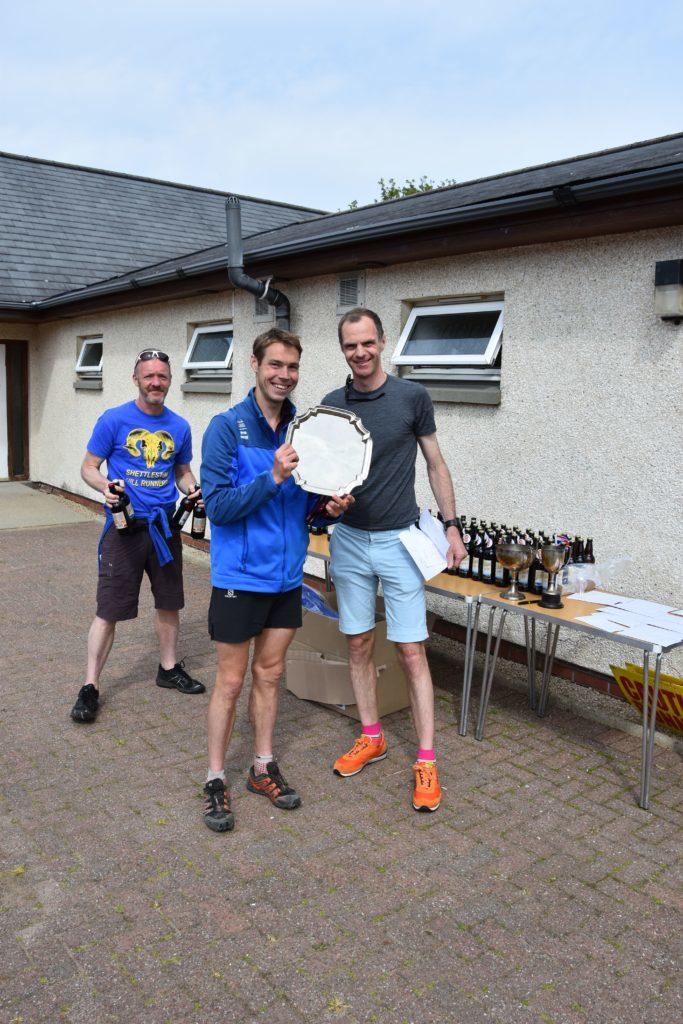 Organiser Peter Mackie of the Shettleston Harriers presents the winners trophy to  Tom Owens.