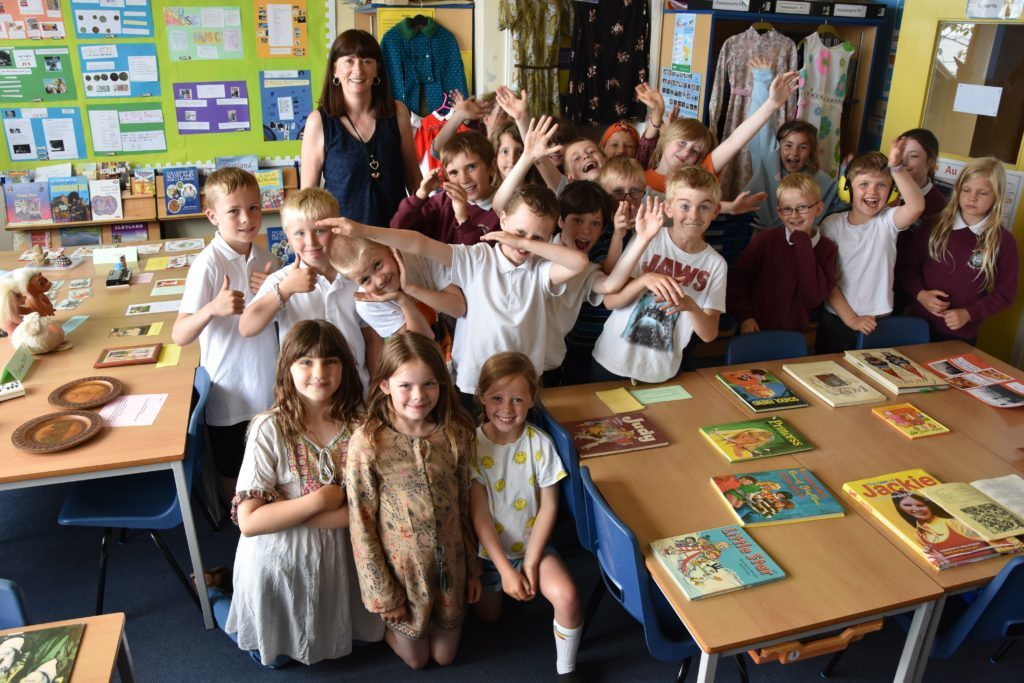 Representing the 1970s, Mrs Catriona Smith and P4/P5 pupils assemble for a class photo.