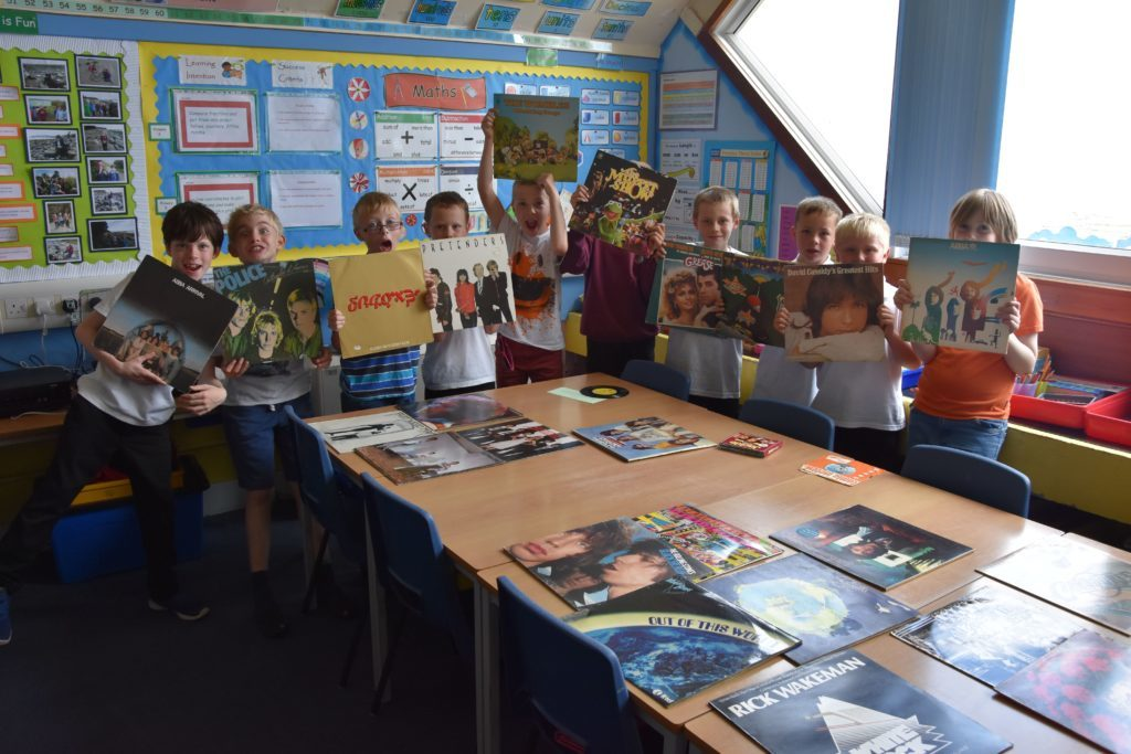 P4/P5 pupils show off some vinyl records from Mrs Catriona Smith's collection.