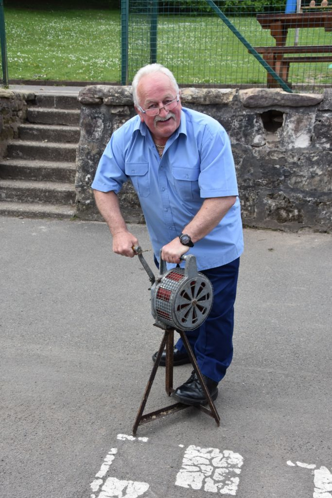 Janitor Allan Little demonstrates a WW2 air raid siren that was donated to the school.