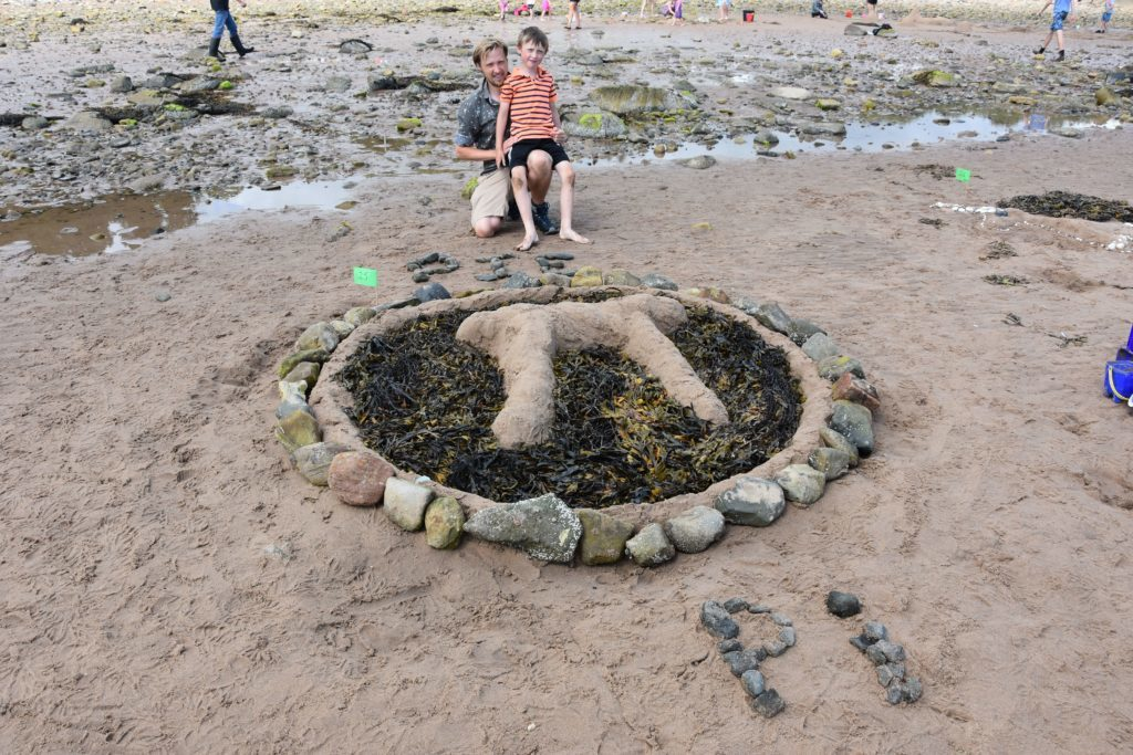 Father and son, young Joseph Cronin from Galashiels with his Pi sandcastle.
