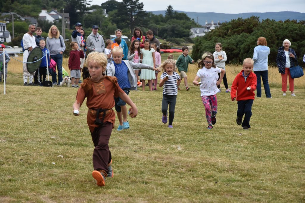 Concentration etched on their faces, children take part in the egg and spoon races.
