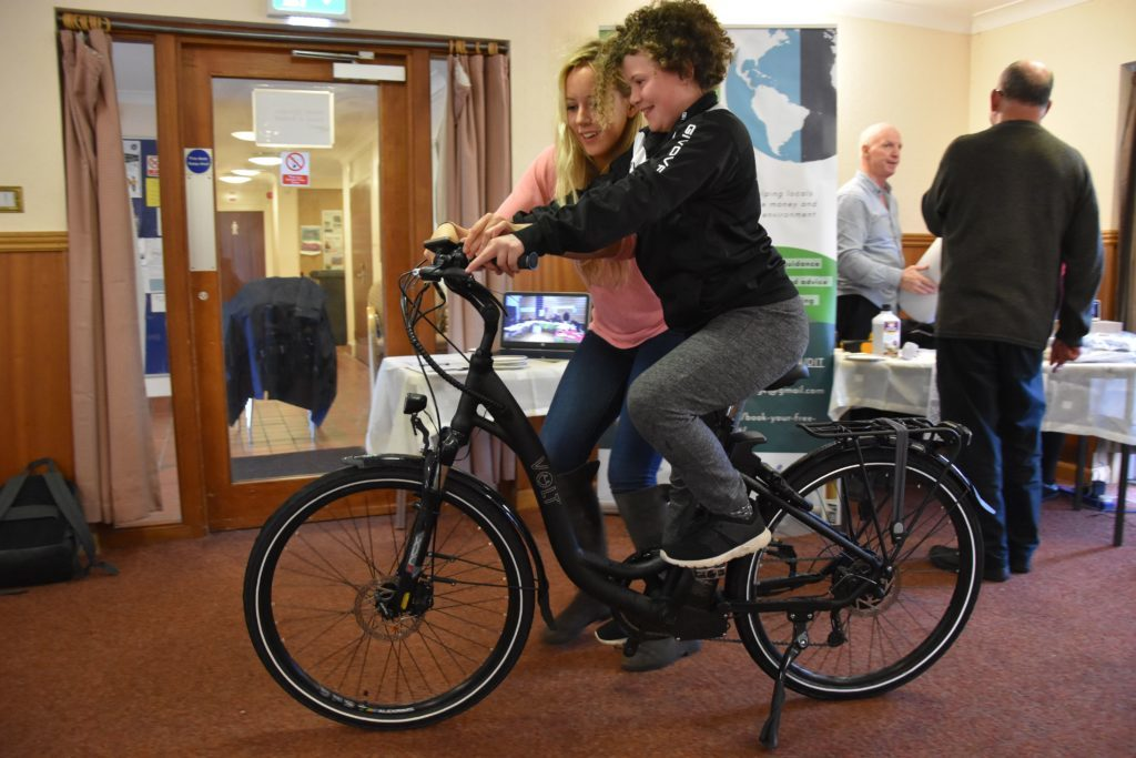 Eco Savvy project manager Judith King shows Caylyn Millar how to operate the electric bicycle.