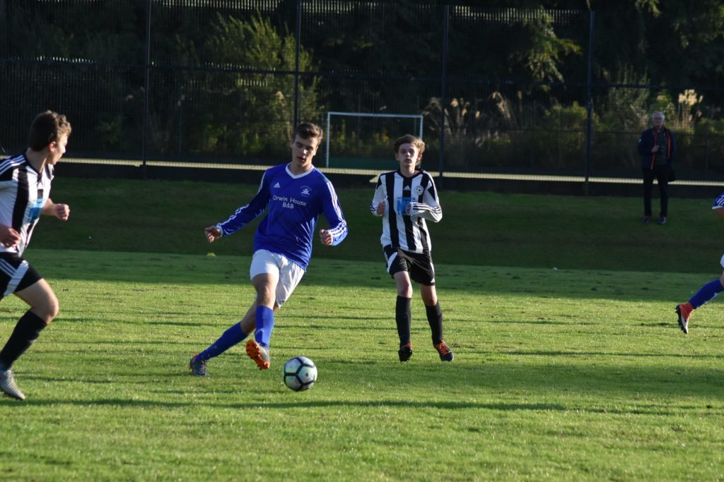 Goal scorer Toby Wingham gains possession of the ball and powers it down the sideline towards the goal.