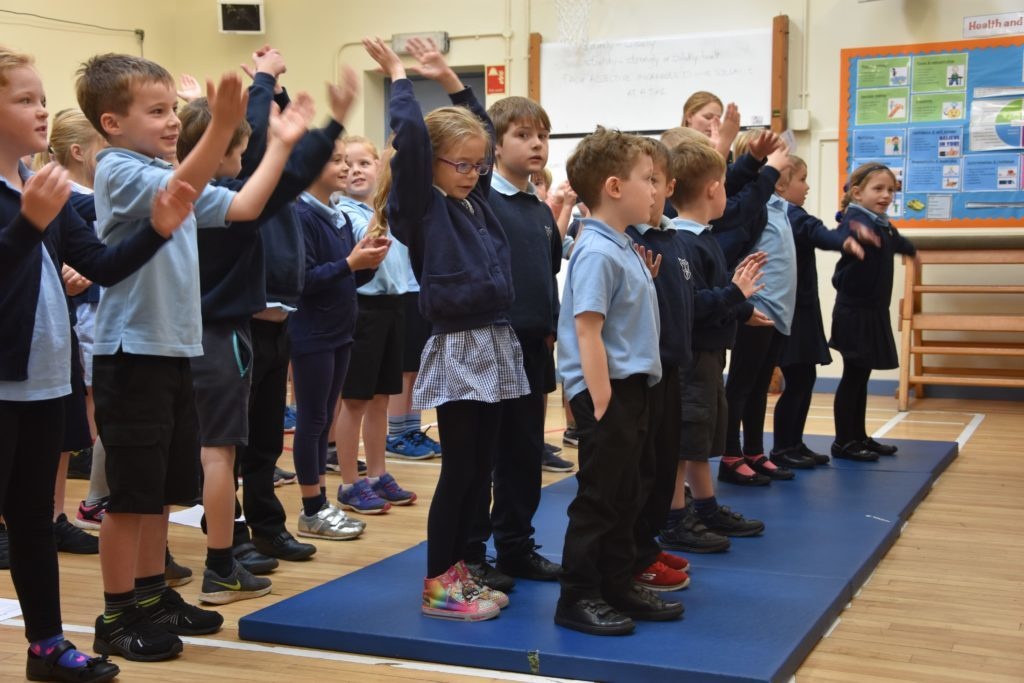 Pupils sing and perform actions for the song Welcome Everybody.