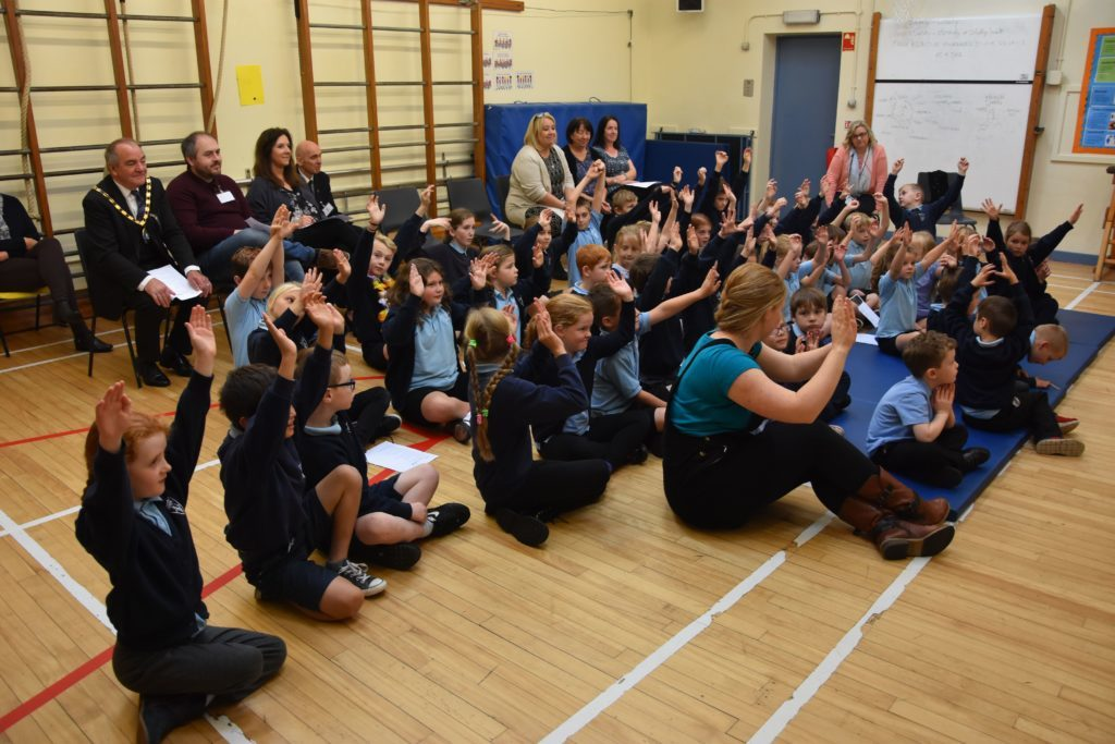 Pupils raise their hands during a fun activity learning about poverty.