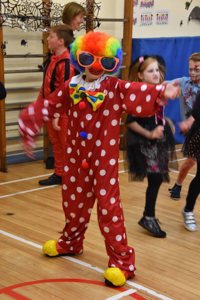 A brightly coloured clown shows off his best dance moves.