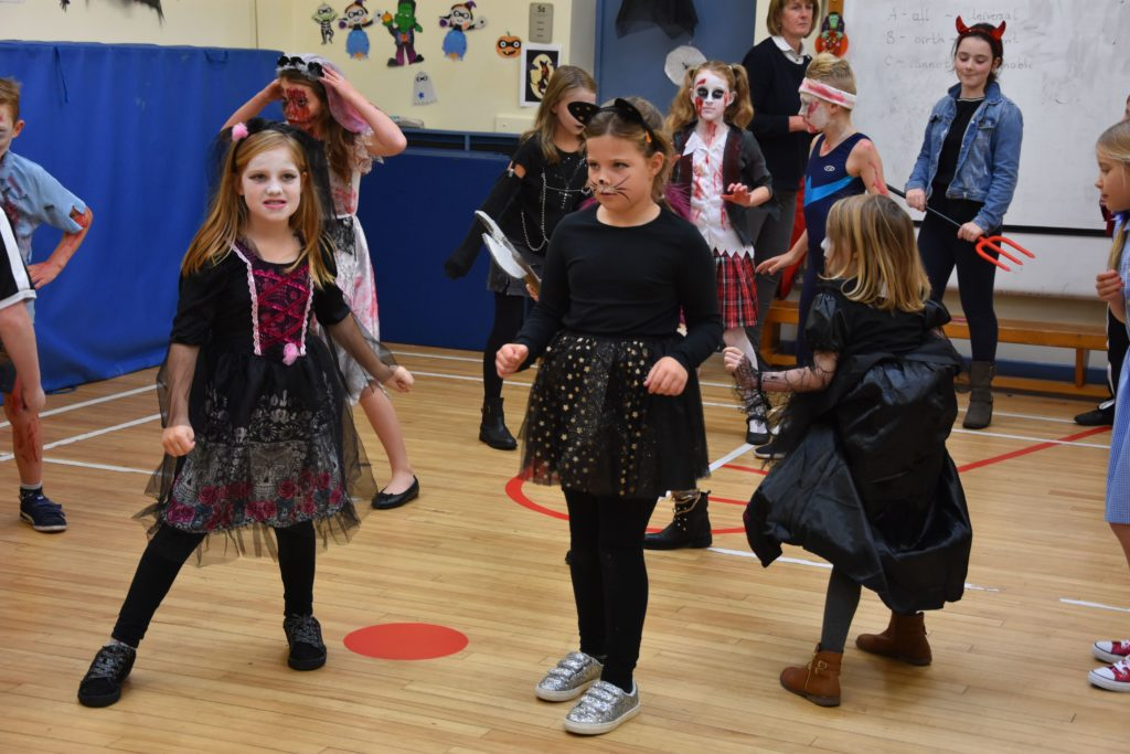 A vampire princess and cat-woman enjoy dancing at their school Hallowe'en party.