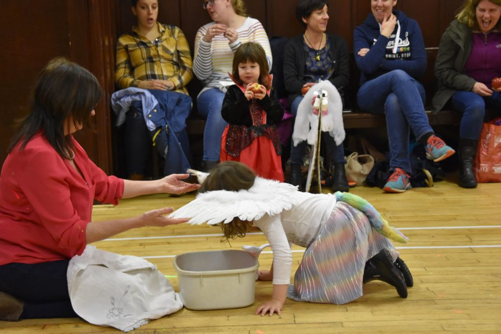 A young dooker gets a hand with her wings while dooking for apples.