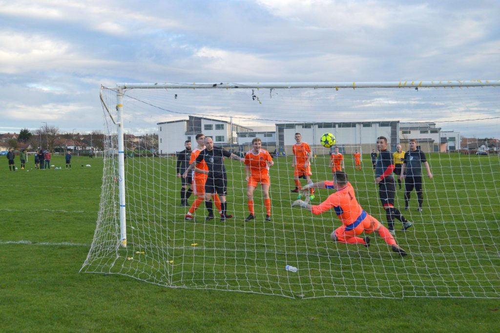 Players look on anxiously as the Galston keeper dives to prevent a goal.