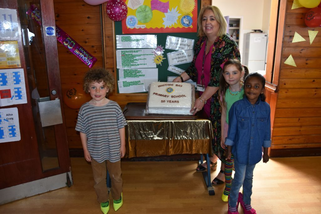 JUNE - Wearing outlandish shoes for their party, Brodie Atkinson, Sera Bibin and Layla Cociuban join Mrs Shirley MacLachlan in showing off their birthday cake celebrating Whiting Bay Primary's 50th birthday .