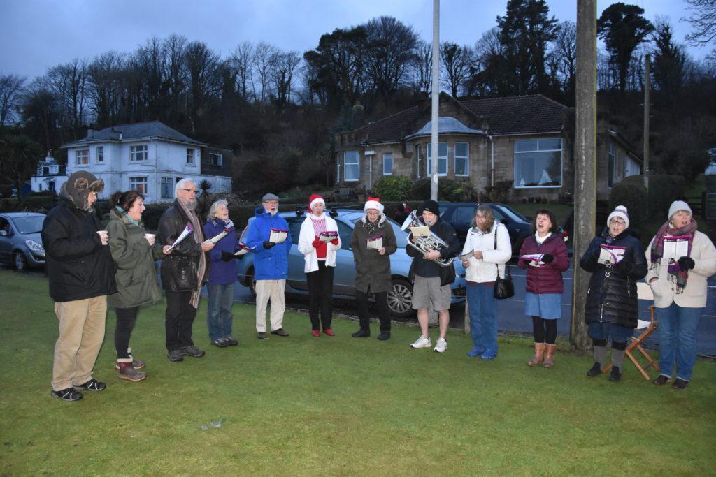 Carol singers lead the crowd in singing traditional Christmas carols.