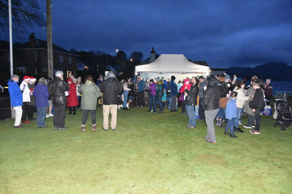 Villagers gather at the village green waiting for the lights to be switched on.