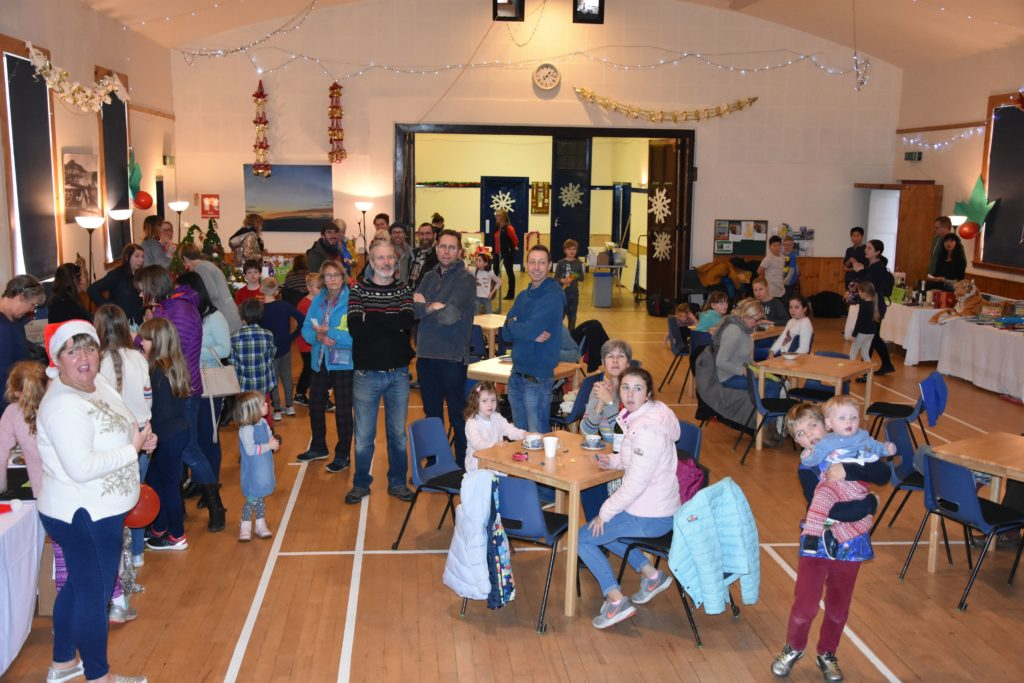 Visitors at the Whiting Bay Primary Christmas Fair listen to the bake-off winner announcement.