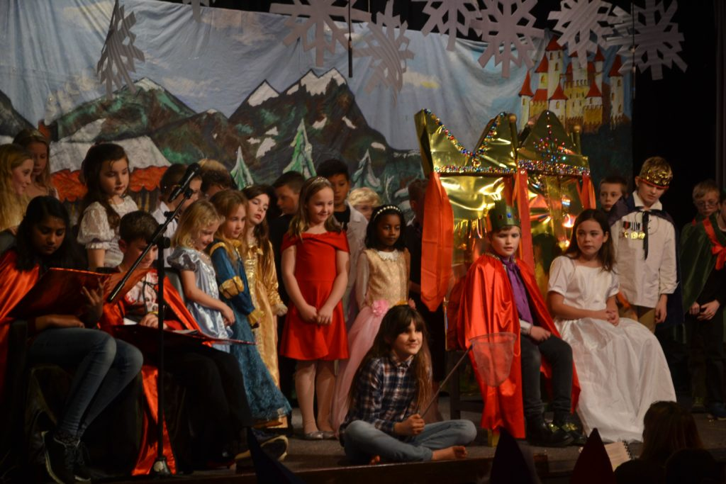 Snow White and the handsome prince are joined on the elaborately decorated stage by all of the characters.