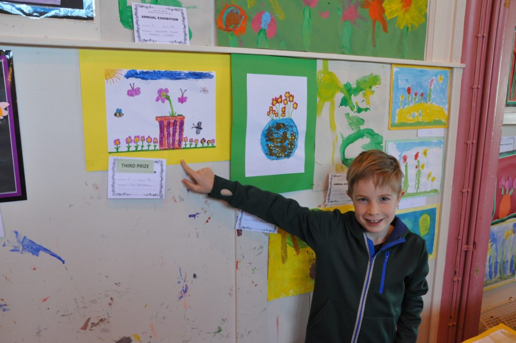 Finn Popplewell proudly shows his Spring themed drawing which won third place in the under eight category.