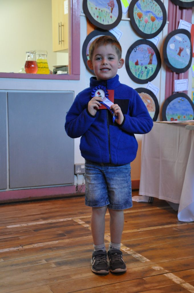 Joey Duncan proudly shows off his rosette for taking second place in the Easter bonnet category.