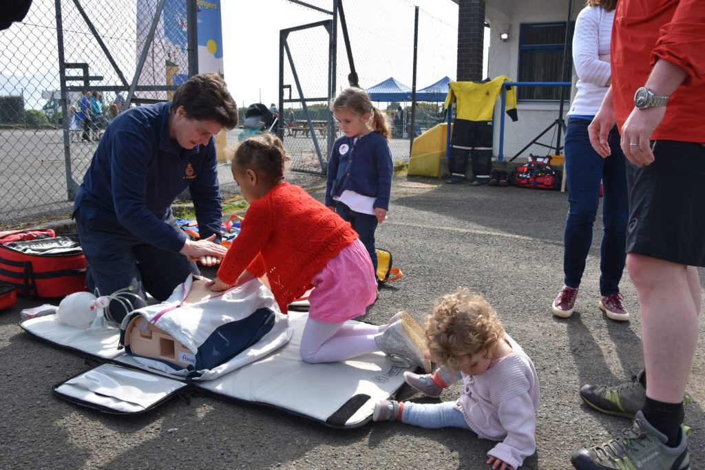 Station officer Fiona Laing demonstrates CPR to young visitors who attended the Coastguard open day in Lamlash.