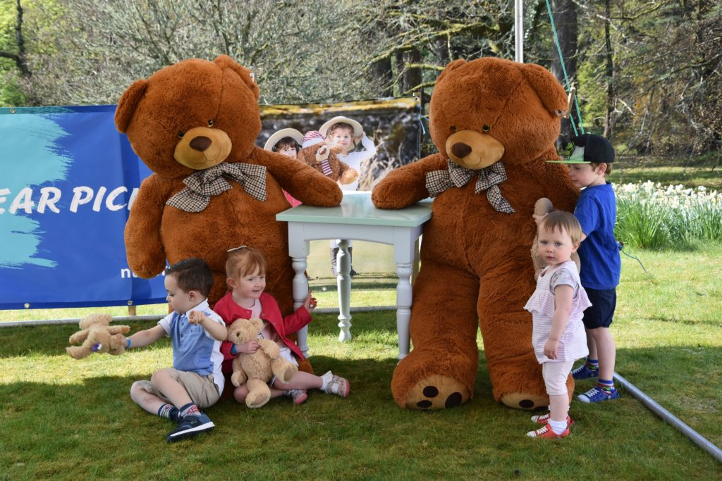 Young children cannot resist the temptation to give the two giant bears a cuddle.