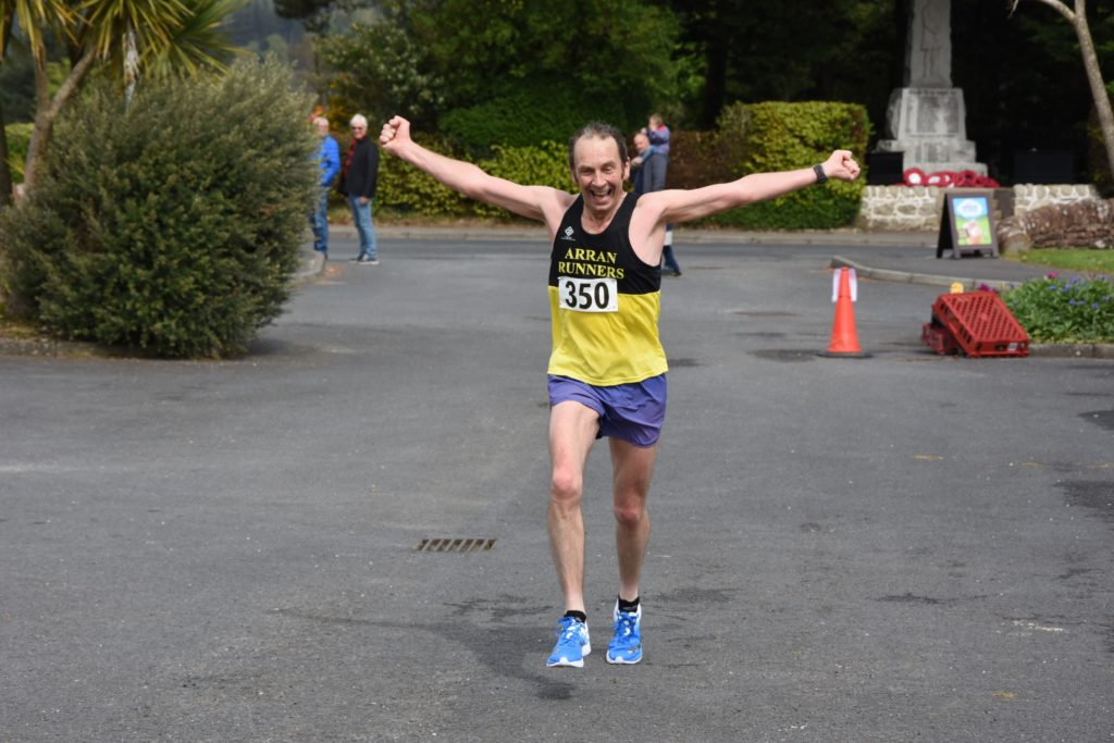 Delighted Arran runner Dave Black crosses the finish line to take the second local male title.