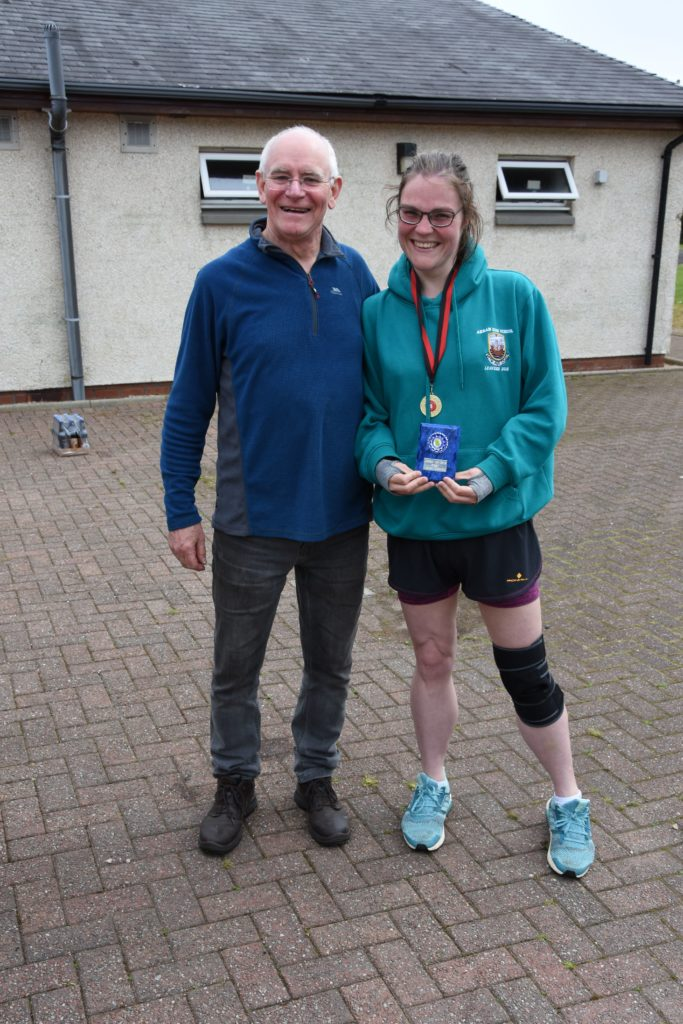 Race organiser Tommy Gilmore presents first local Julia Harrison with her trophy.