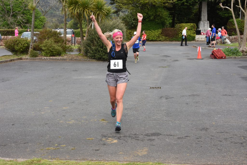 Local runner Zara Mackay crosses the finish line.