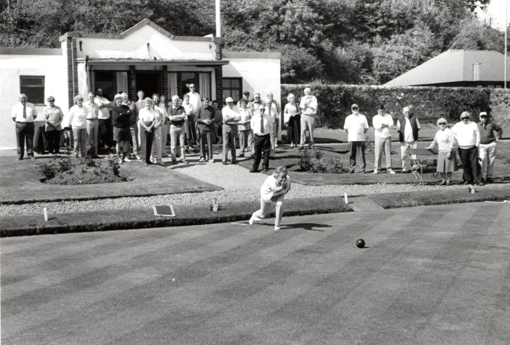 Margaret Murchie throws the first bowl of the season at Lamlash Bowling Club last Saturday while club members look on in anticipation of getting on the green themselves.