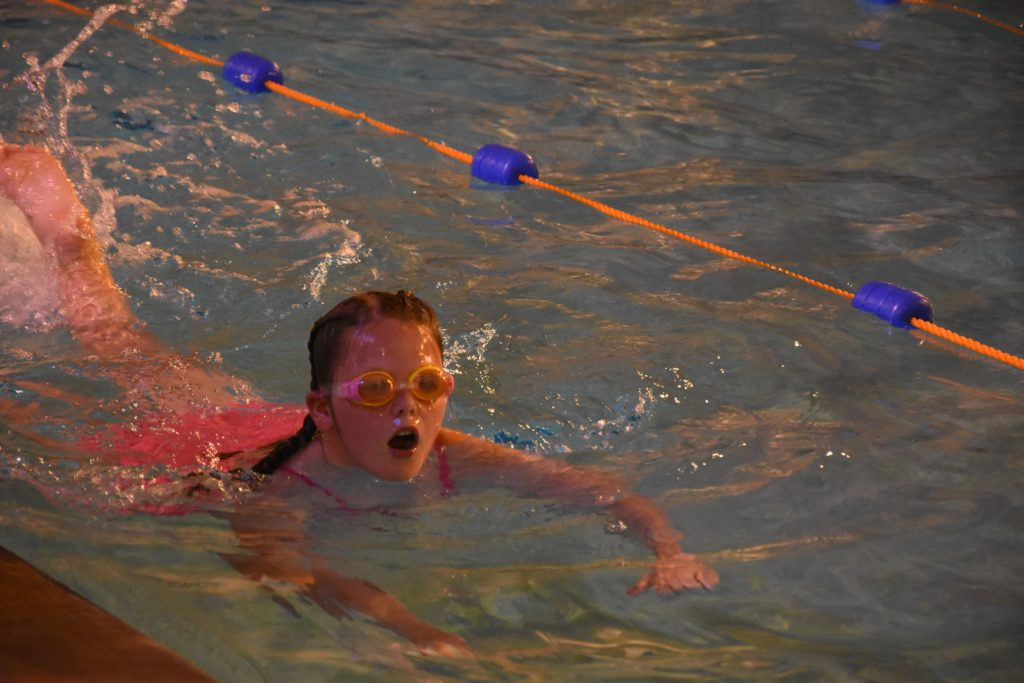 A young swimmer comes up for air.