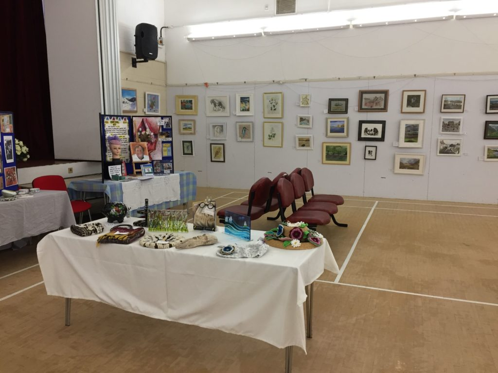 A table at last year's event shows just some of the varied mediums on display, including glasswork, tidal art, folk painting and weaving.