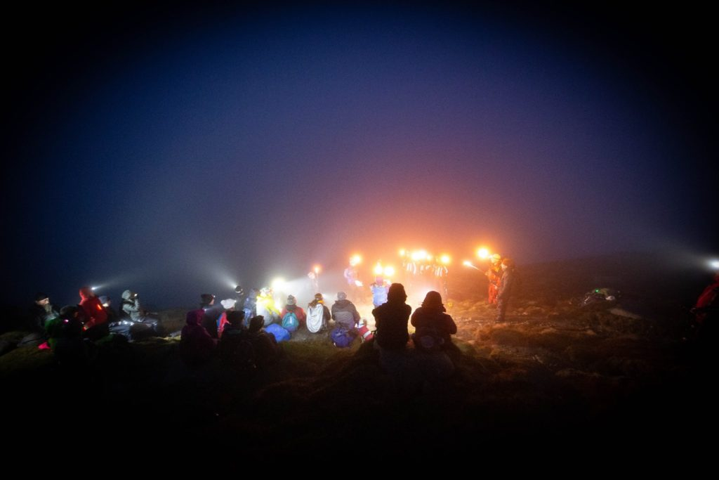 Warmly dressed participants light up the summit of Goatfell with their torches and the flaming beacon.