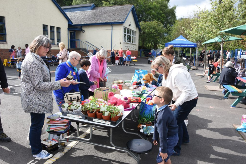A young Brodick Primary pupil makes a sale at the plant and bric-a-brac stall.