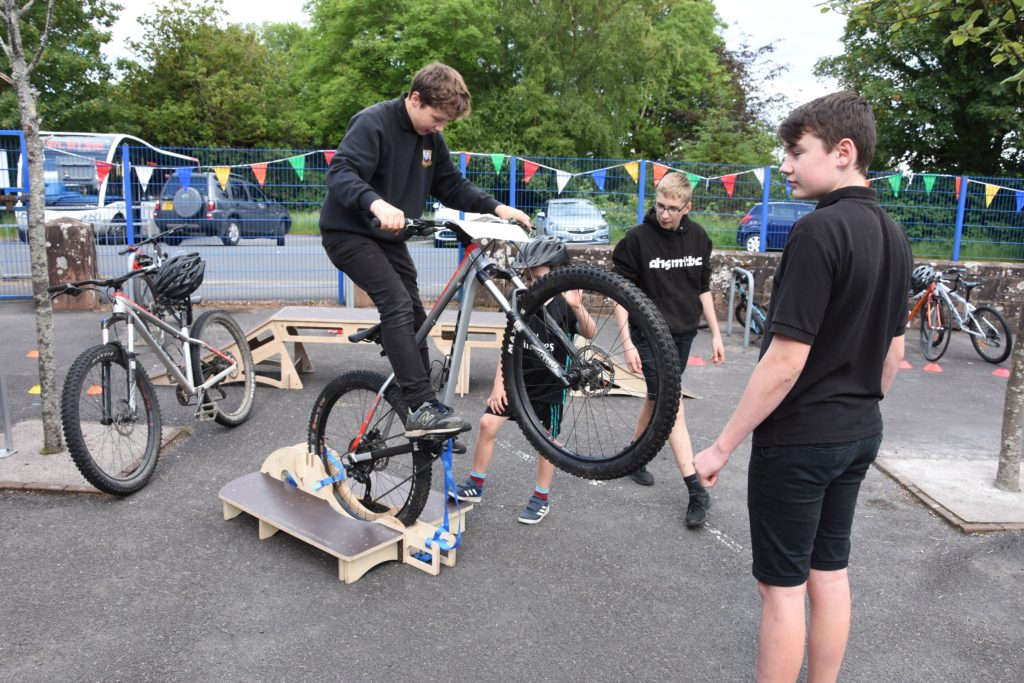 An Arran High School Mountain Bike Club member demonstrates how the Manual Master machine works.