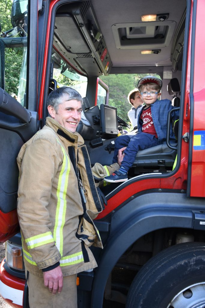 A friendly fireman allows a young boy to sit in the fire engine.