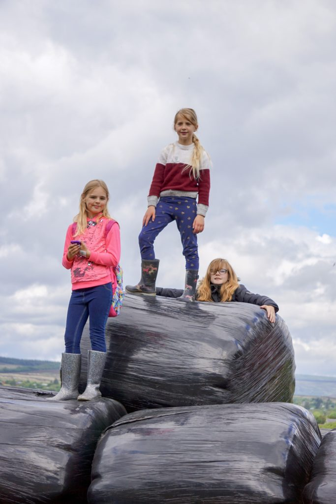 Girls climb onto of the silage bales in the fields.