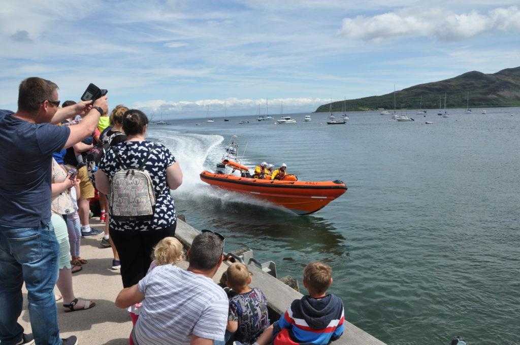 The lifeboat speeds past Lamlash pier.