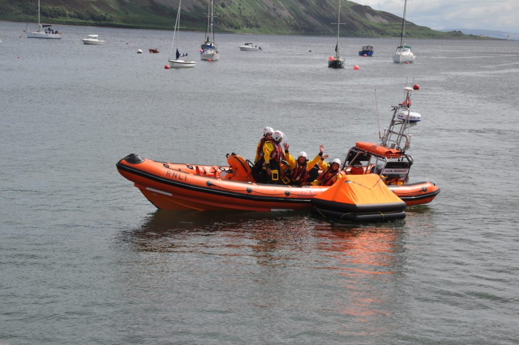 The lifeboat crew wave to the crowd.