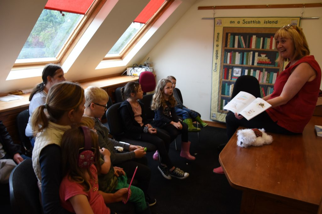 Children listen intently to the story of The Tattoo Toorie by Arran author Alison Page.