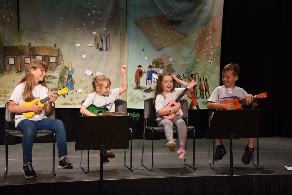 Young ukulele players react to the hearty applause from the audience.
