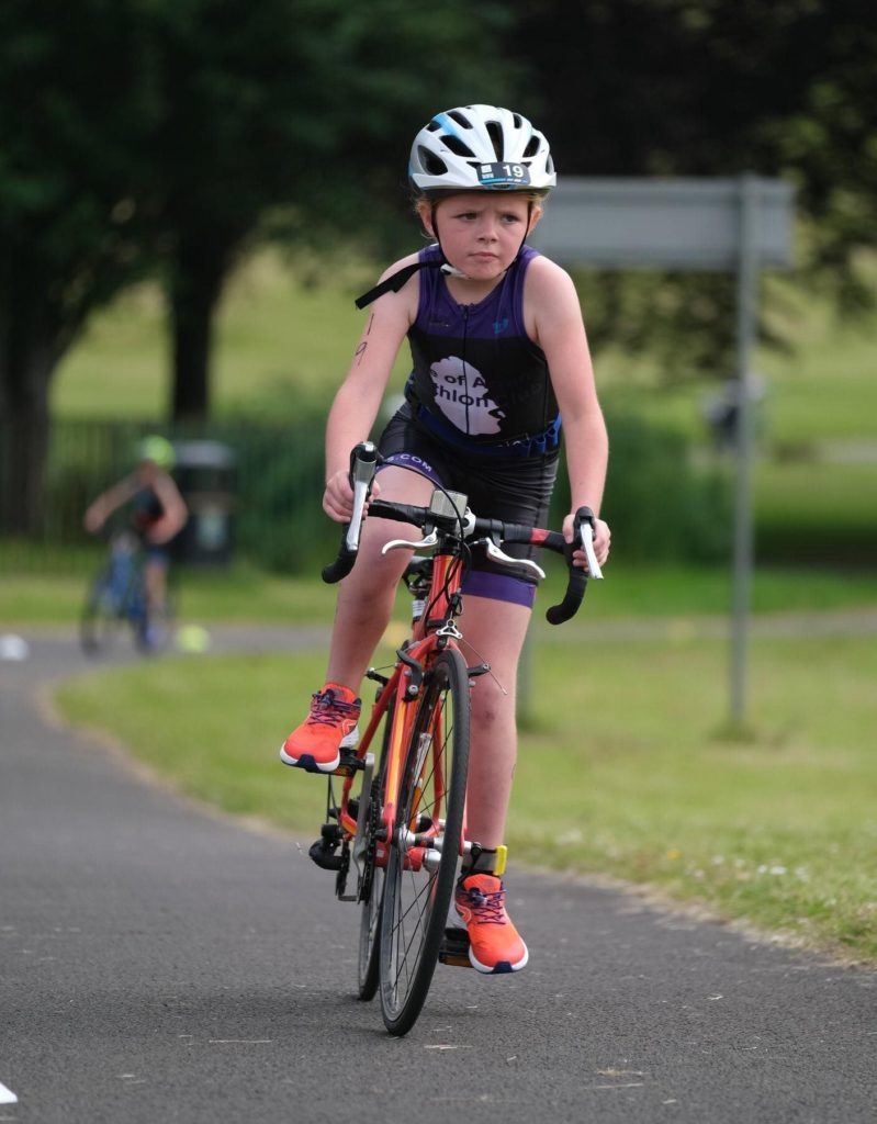 Concentration etched on her face, Isla works her way up the field during the bike section of the triathlon. Photo: ImacImages Sports Photography.