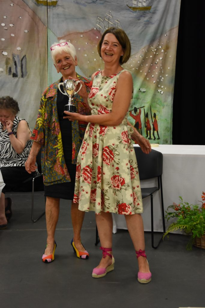 Nici Sketchley-Kaye receives the Arran Provisions Trophy from honorary guest Gisela Creed.